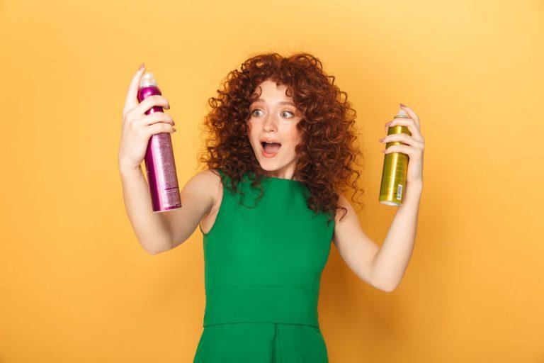 Pelirroja de cabello rizado con dos latas de spray